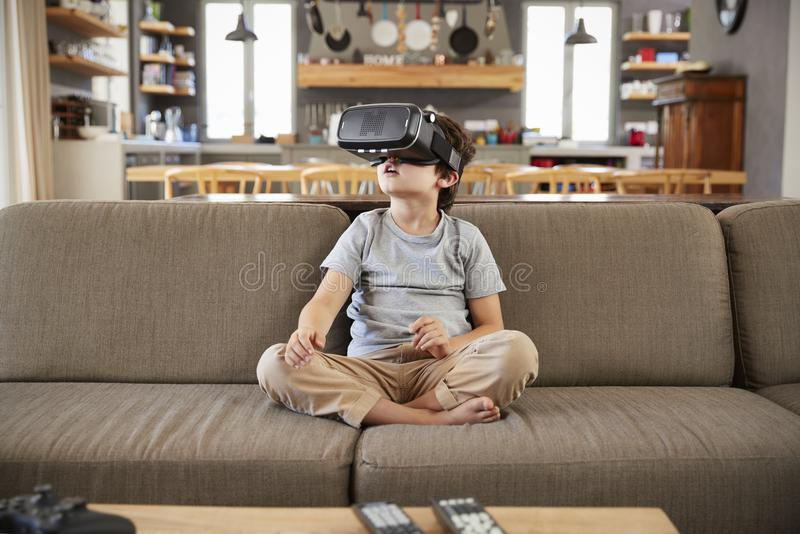 Muchacho que se sienta en Sofa Wearing Virtual Reality Headset foto de archivo