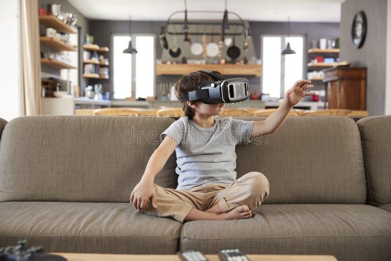 Muchacho que se sienta en Sofa Wearing Virtual Reality Headset fotografía de archivo