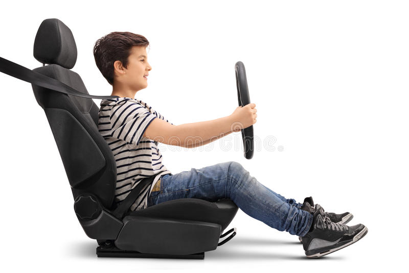Muchacho que se sienta en un asiento de carro que finge conducir imagenes de archivo