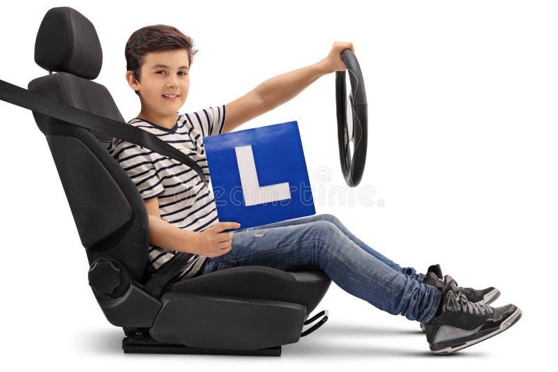 Muchacho que se sienta en un asiento de carro y que muestra una L-muestra fotografía de archivo libre de regalías