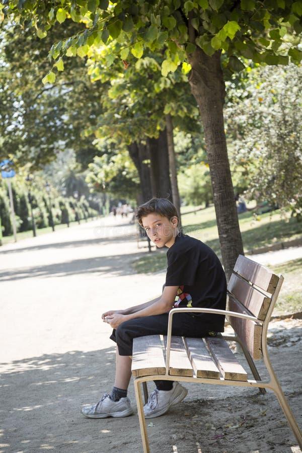 Muchacho que se sienta en un banco en un parque fotos de archivo libres de regalías