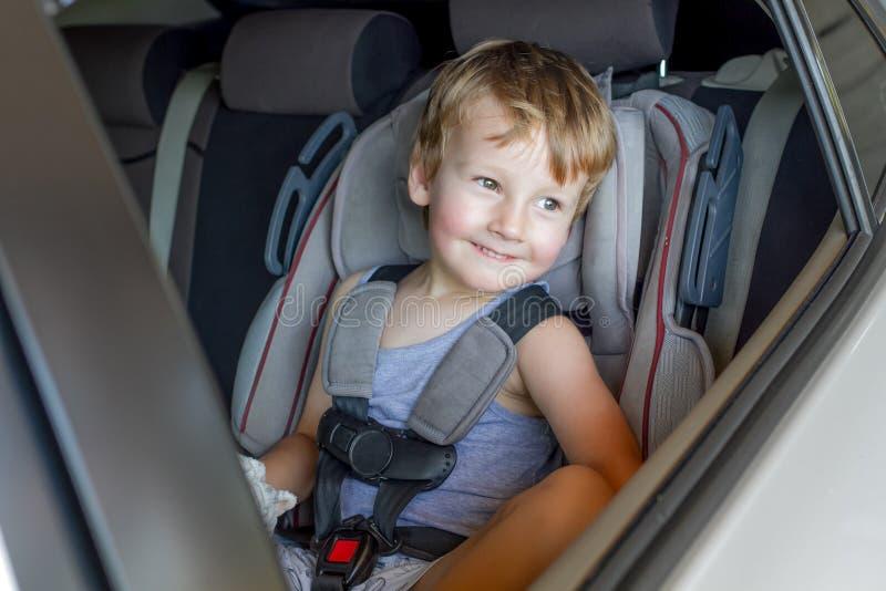 Muchacho que se sienta en un coche en silla de la seguridad imágenes de archivo libres de regalías