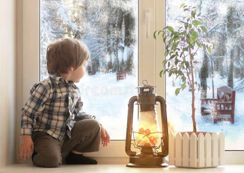 Muchacho que se sienta en un travesaño blanco y miradas de la ventana hacia fuera la ventana foto de archivo libre de regalías