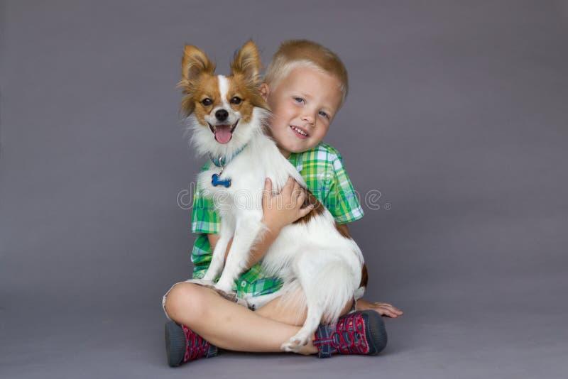 Muchacho que se sienta que sostiene el perro de Papillon fotos de archivo