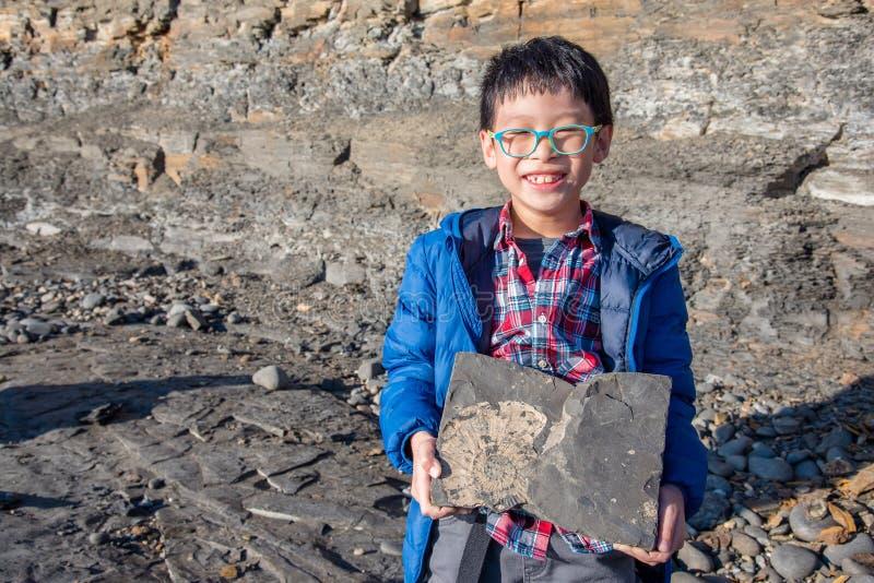 Muchacho que se sostiene de piedra con el fósil dentro fotos de archivo libres de regalías