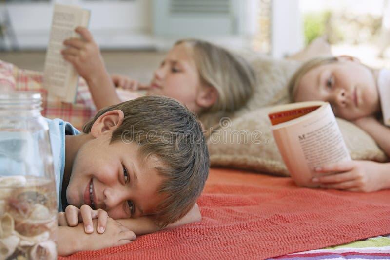 Muchacho que sonríe con los libros de lectura de las hermanas en el pórtico fotografía de archivo