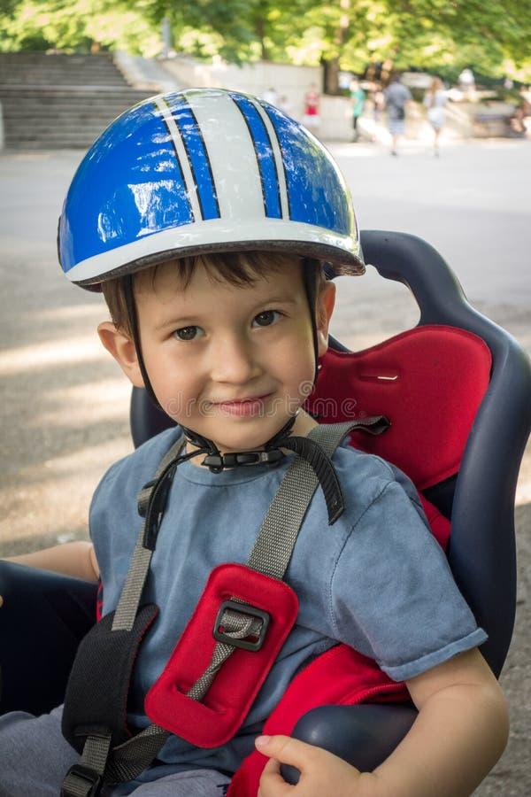 Muchacho que sonríe en la bicicleta del asiento El niño tiene casco biking Protección en la bicicleta foto de archivo libre de regalías