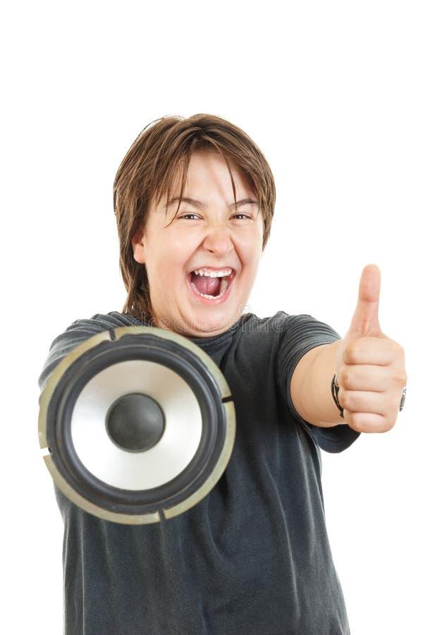 Muchacho que sonríe y que presenta con confianza con el pulgar para arriba con el altavoz fotos de archivo libres de regalías
