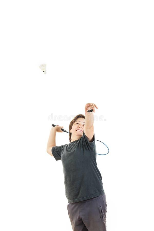Muchacho que sonríe y que sostiene la estafa de bádminton y que intenta golpear la bola imágenes de archivo libres de regalías