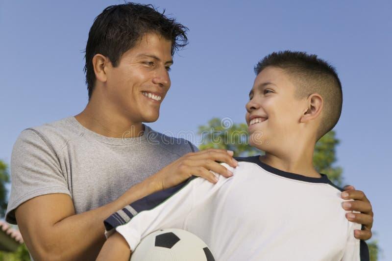 Muchacho (13-15) que sostiene el balón de fútbol con el hombre joven fotografía de archivo libre de regalías