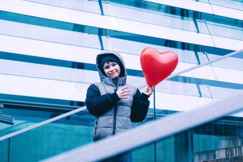 Muchacho que sostiene el globo en forma de corazón en arquitectura urbana imagenes de archivo