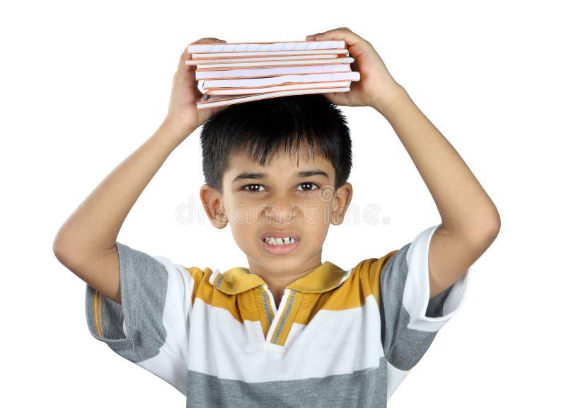 Muchacho que sostiene el libro de texto con la expresión imagen de archivo libre de regalías