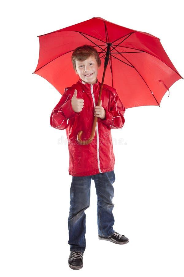 Muchacho que sostiene el paraguas rojo sobre el fondo blanco fotografía de archivo libre de regalías