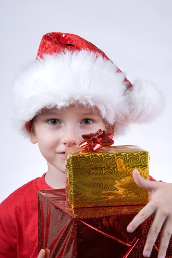 Muchacho que sostiene los regalos de una Navidad imagenes de archivo
