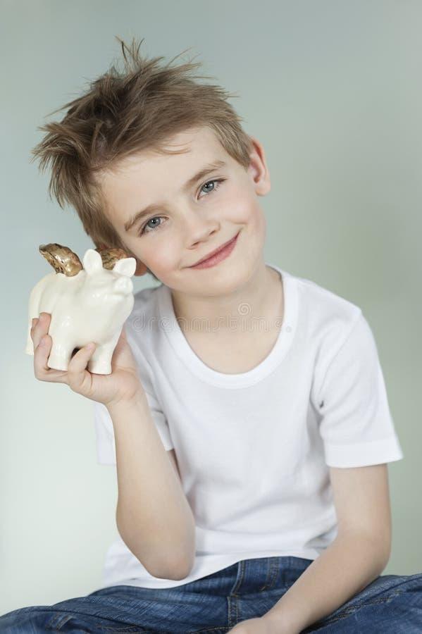 Muchacho que sostiene una hucha sobre fondo gris fotografía de archivo libre de regalías
