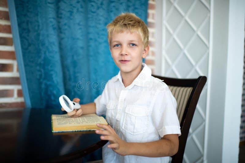 Muchacho que sostiene una lupa imagenes de archivo