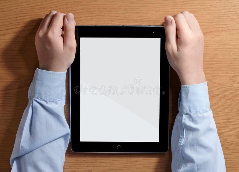Muchacho que sostiene una tableta que se sienta en la tabla imagen de archivo libre de regalías