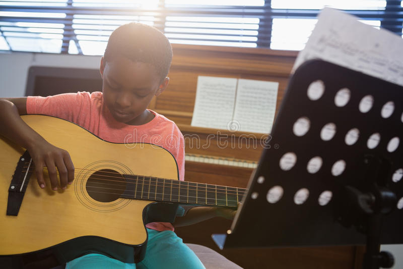 Muchacho que toca la guitarra mientras que se sienta en sala de clase fotos de archivo