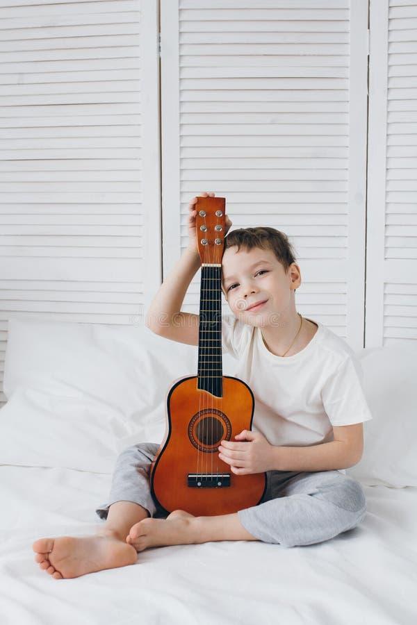 Muchacho que toca una pequeña guitarra que se sienta en la cama fotos de archivo libres de regalías