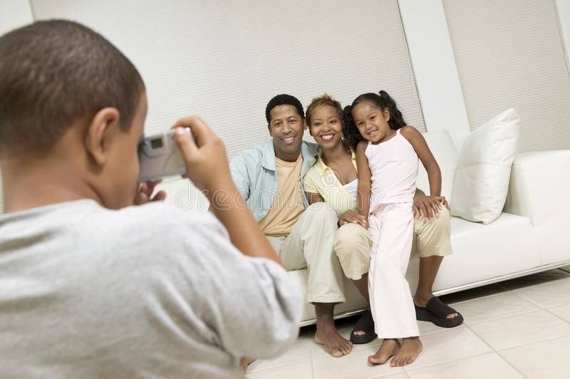 Muchacho que toma el cuadro de la familia en el sofá fotografía de archivo