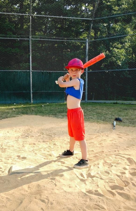 Muchacho que toma práctica que golpea de béisbol fotografía de archivo