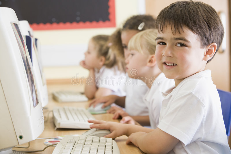 Muchacho que trabaja en un ordenador en la escuela primaria fotos de archivo libres de regalías