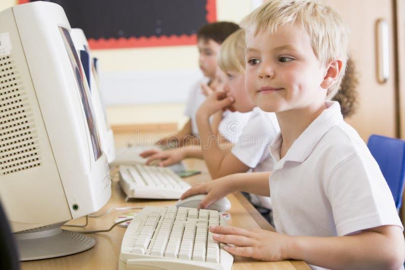 Muchacho que trabaja en un ordenador en la escuela primaria imágenes de archivo libres de regalías