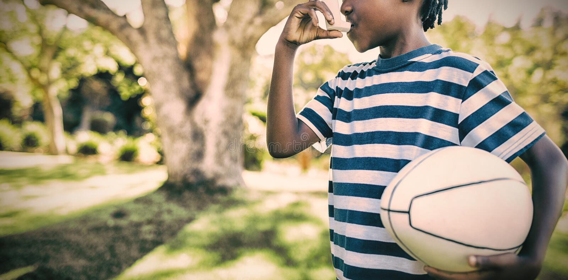 Muchacho que usa el inhalador del asma en el parque fotografía de archivo libre de regalías