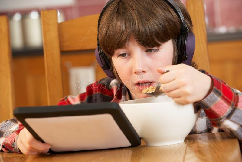Muchacho que usa el ordenador de la tablilla mientras que come el desayuno imágenes de archivo libres de regalías