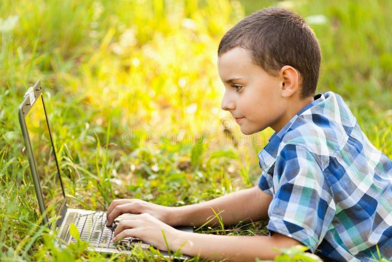 Muchacho que usa la computadora portátil al aire libre fotos de archivo libres de regalías
