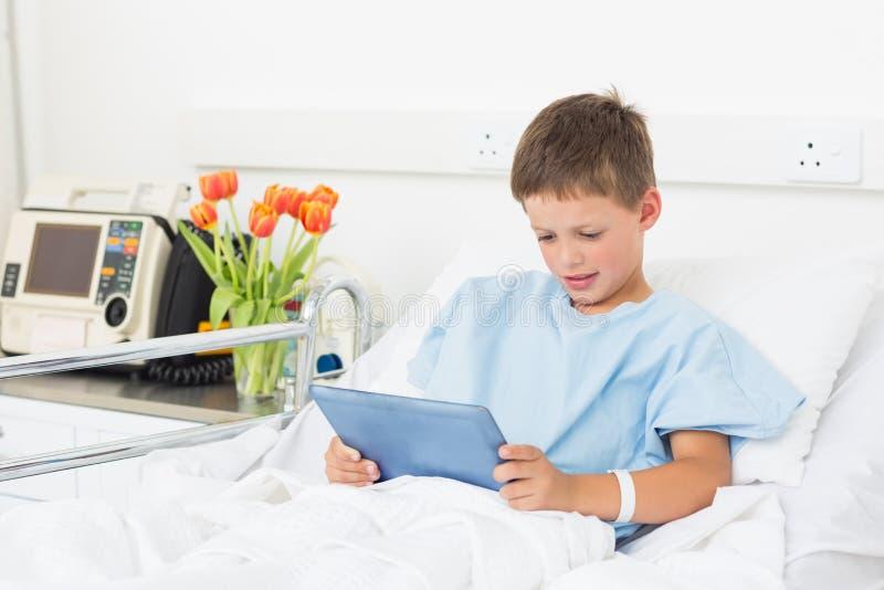 Muchacho que usa la tableta digital en hospital imagen de archivo