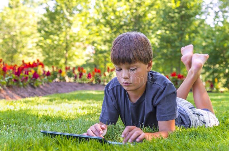 Muchacho que usa su ordenador portátil al aire libre en parque fotografía de archivo libre de regalías