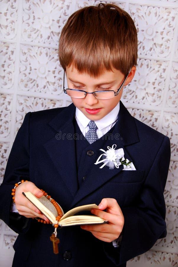 Muchacho que va a la primera comunión santa foto de archivo