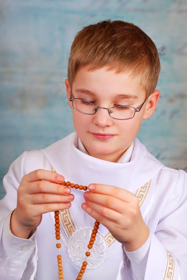 Muchacho que va a la primera comunión santa con el rosario fotos de archivo libres de regalías