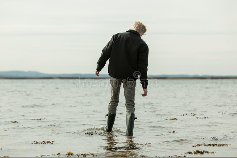 Muchacho que vadea en el agua que se mueve adentro durante alta marea imagen de archivo