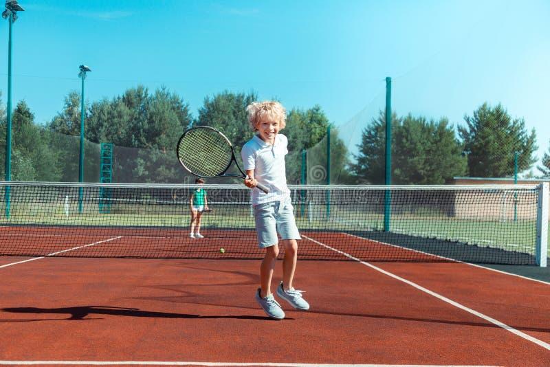 Muchacho rizado alegre que siente feliz mientras que juega a tenis afuera imagen de archivo libre de regalías