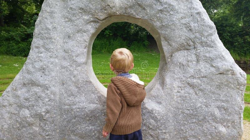 Muchacho rubio caucásico que mira a través de escultura foto de archivo