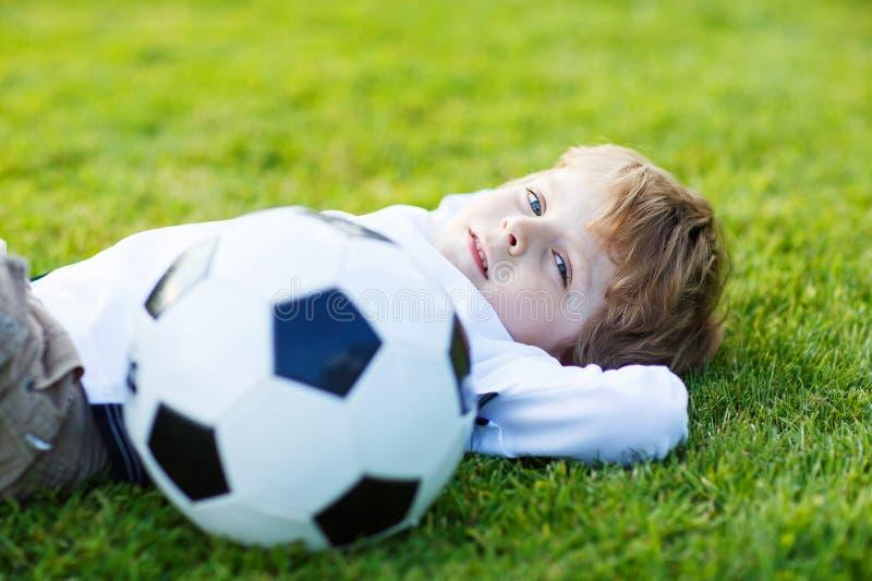 Muchacho rubio de 4 que descansan con fútbol en campo de fútbol foto de archivo libre de regalías