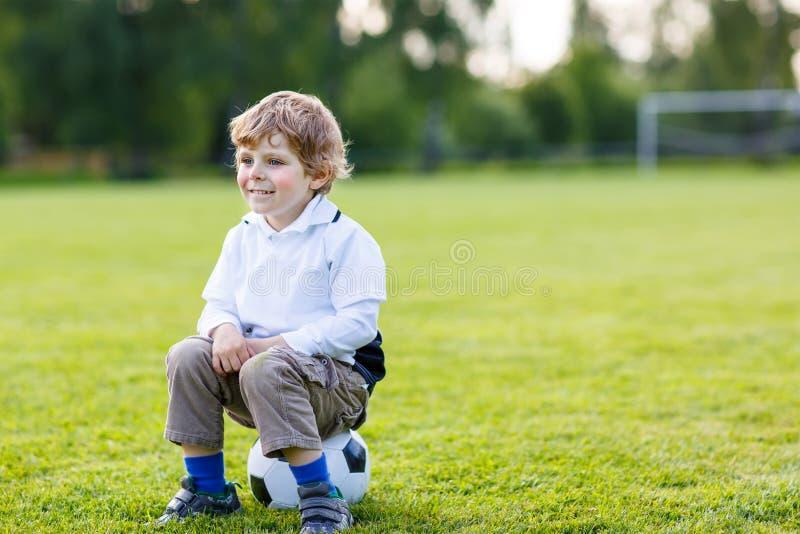 Muchacho rubio de 4 que descansan con fútbol en campo de fútbol imagenes de archivo