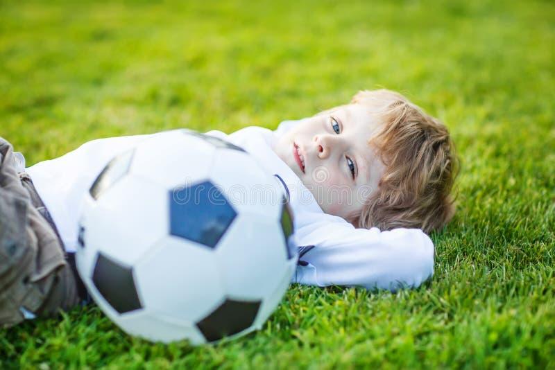 Muchacho rubio de 4 que descansan con fútbol en campo de fútbol fotos de archivo