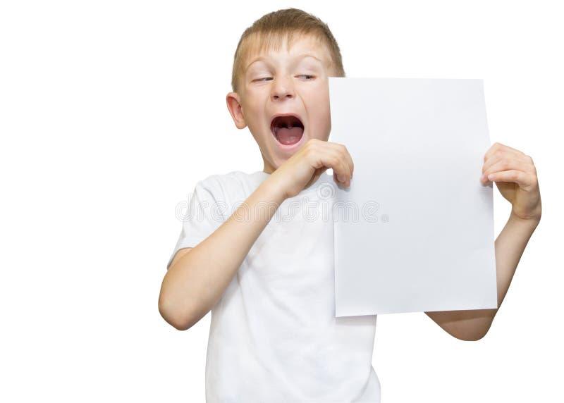 Muchacho rubio emocional en una camisa blanca con una hoja de papel gris para las notas sobre un fondo blanco foto de archivo