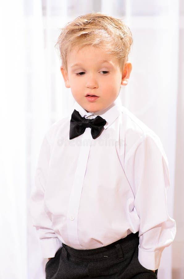 Muchacho rubio en la camisa blanca con la corbata de lazo negra imágenes de archivo libres de regalías