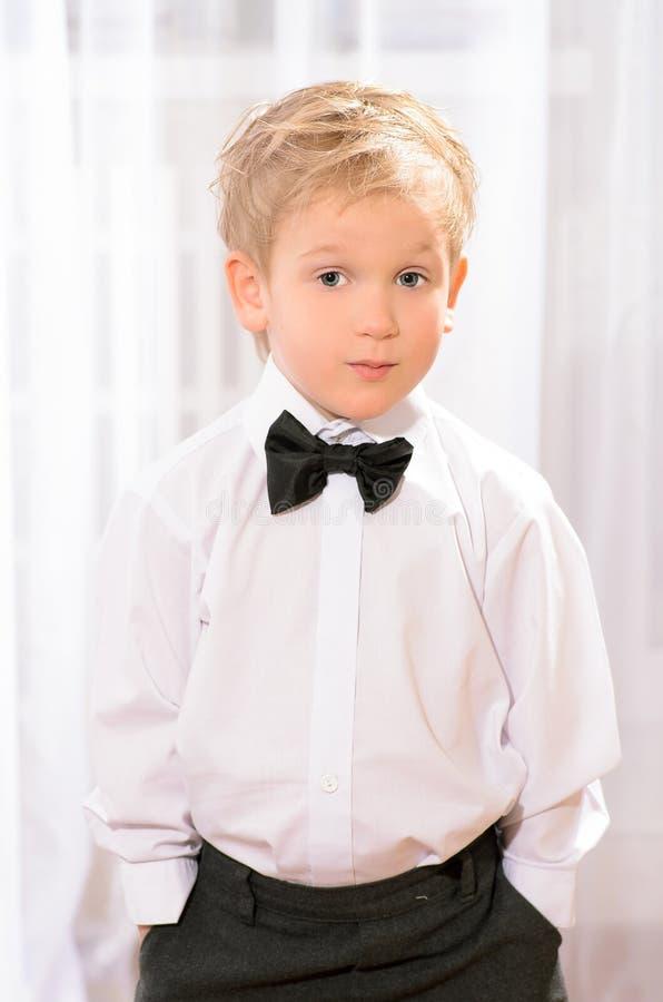 Muchacho rubio en la camisa blanca con la corbata de lazo negra foto de archivo libre de regalías