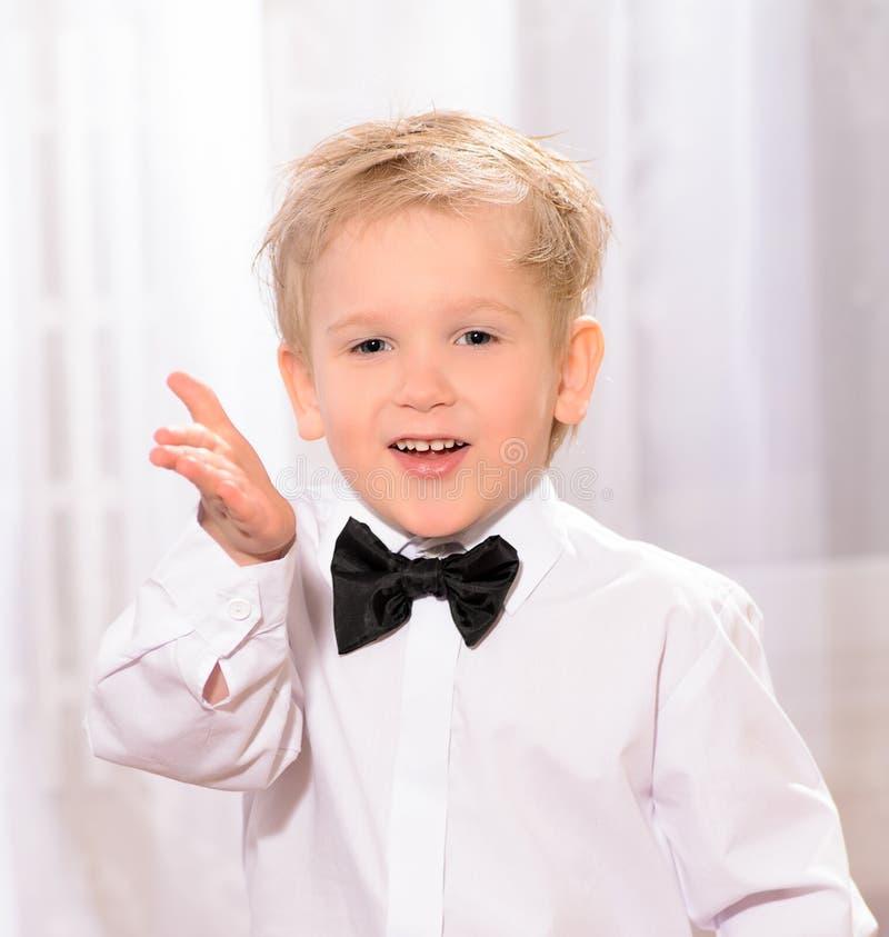 Muchacho rubio en la camisa blanca con la corbata de lazo negra fotografía de archivo libre de regalías