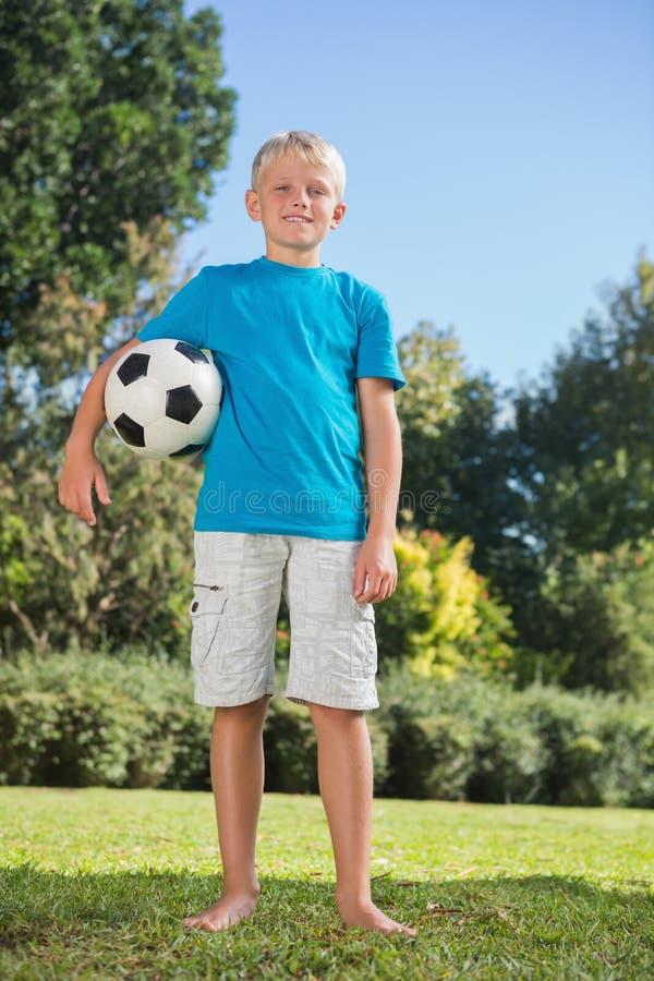 Muchacho rubio joven que lleva a cabo fútbol imagenes de archivo