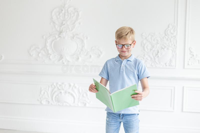 Muchacho rubio joven que presenta en un fondo de la pared blanca con el libro de texto verde en manos imágenes de archivo libres de regalías