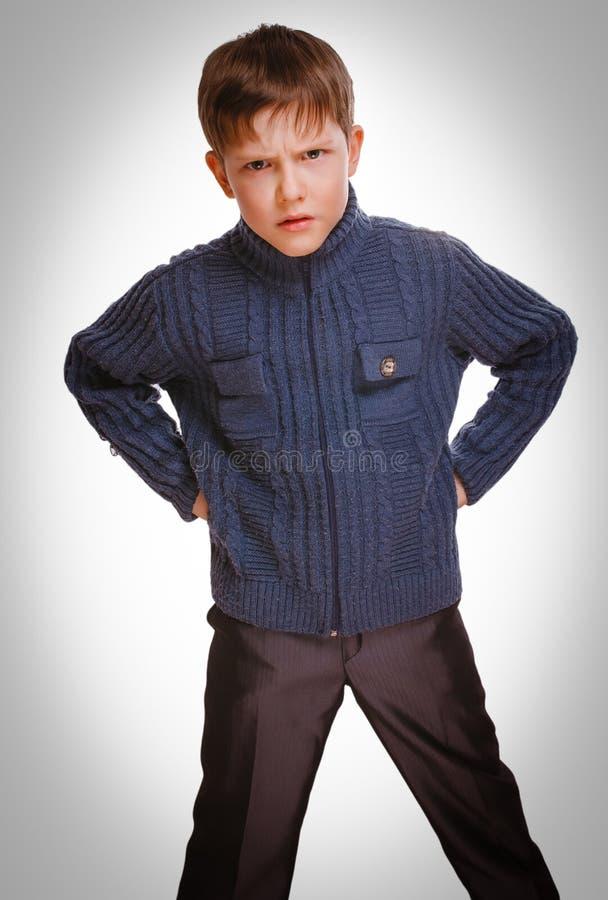 Muchacho rubio melancólico del niño enojado malvado agitado gris en suéter rayado imágenes de archivo libres de regalías