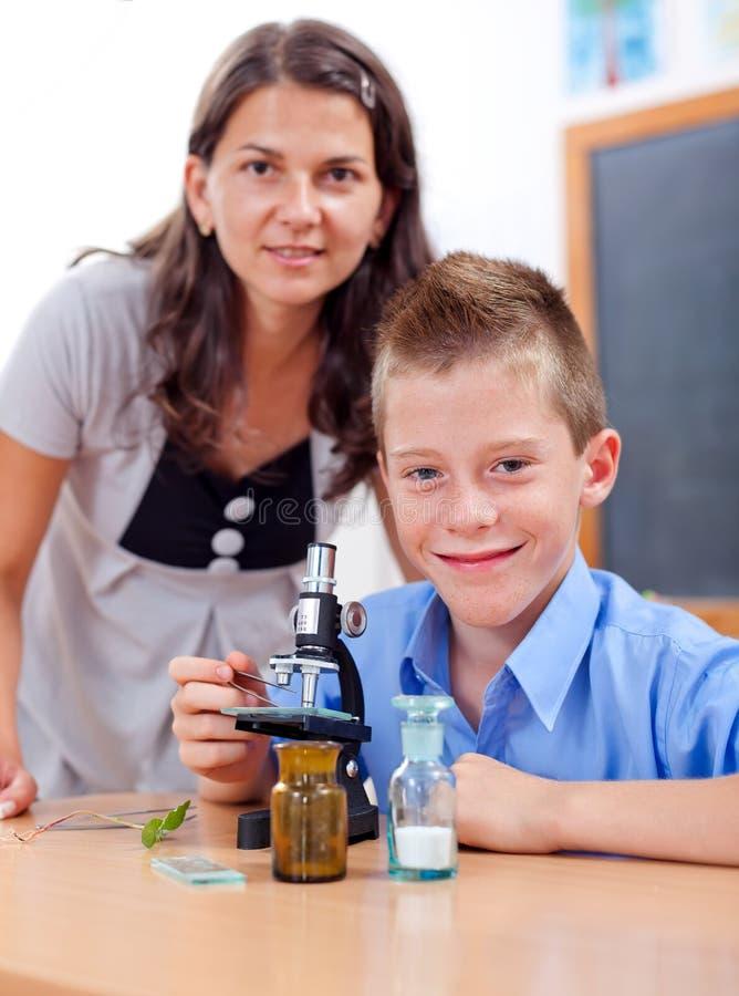 Muchacho sabio con el microscopio y el profesor fotos de archivo