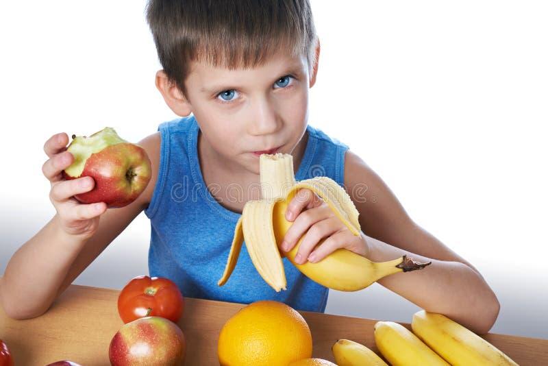 Muchacho sano feliz que come el plátano y la manzana aislados foto de archivo