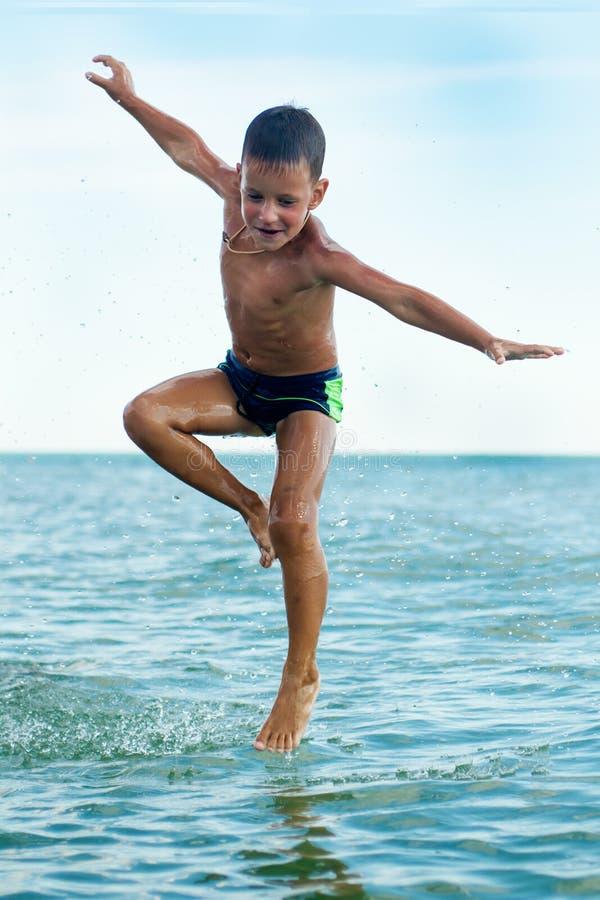Muchacho sano que salta en agua fotos de archivo